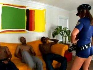 Hvit dama i politi uniform blir pult av to svarte karer
